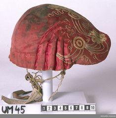 Mössan har styv stomme av papp, dock ganska tunn och sladdrig. Yttertyg av rött siden. Enligt text från 1917 i gåvobok purpurfärgad. Fodertyg av smårutigt linne i blått och vitt (gulnat, mörknat). Rester av ljusrött sidenband längs nederkanten. Broderi i tambursöm med silke. Ett stiliserat mönster med blommor, blad, linjer och cirklar. Mönstret finns framtill och på sidoflikarna. Inget mönster mitt på kullen och bak. Färgerna i broderiet är vitt, mycket ljust blågrönt och ljusgult. Fem veck…