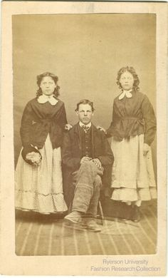 Two Women Standing And Man Sitting Unknown Photographer Date Location Are Wearing Identical Outfits