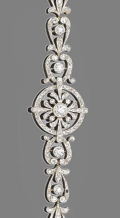A diamond bracelet, circa 1900  The articulated row of old brilliant and single-cut diamond scrolling links, set to the centre with a similarly-cut diamond circular pierced plaque, diamonds approx. 1.95ct total, length 14.4cm