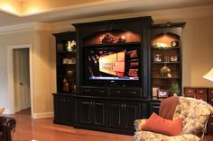 Fascintng Black Entertainment Center Cabinets in Family Room with Flat Screen tv and Cozy Leather Chiar and Wooden Flooring Idea