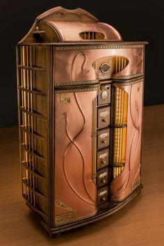Jugendstilkommode aus massivem Buchenholz, mit Kupfer beschlagen. Integrierte Beleuchtung, mechanische Uhr und Geheimfach.