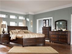 Dark brown wood bedroom furniture with dark smokey blue walls, white bedding, dark wood floor, a light brown rug, white curtains on big windows, and white/light brown/blue accents…would be a place I'd like to spend some time…with you.