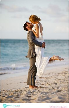 Groom picking up bride on the beach. Destination wedding in Turks and Caicos at The Somerset. Brilliant Studios.