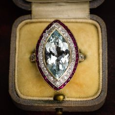 An astonishing Edwardian era marquise cluster ring, set with a central aquamarine framed by a double halo of diamonds and rubies.