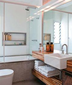 13. O banheiro alterna cimento queimado, teca e laminado, aplicado no boxe. U...