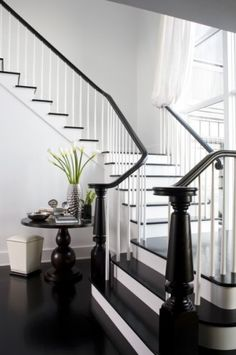 Dark stairs with white banister. Like the combo of rich wood and white.