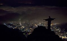 """Rio During Earth Hour     Photograph by Felipe Dana, AP Silhouetted against still bright city lights below, Rio de Janeiro's """"Christ the Redeemer"""" statue goes dark for Earth Hour 2011 on Saturday night.  The Brazilian icon joined the Empire State Building, the Eiffel Tower, Beijing's Forbidden City, and hundreds of other world landmarks that were abruptly blacked out from 8:30 to 9:30 p.m., local time."""