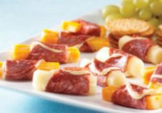 string cheese or colby jack sticks wrapped in salami with a mustard sauce. Served with crackers and grapes.