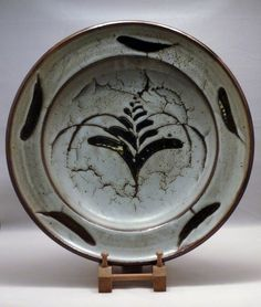 """sig1721 Stoneware charger, thick crawling white dolomite glaze over rich tenmoku.  Wax resist """"foxglove"""" motif in the well and dash decoration to the rim.  Impressed DL mark.  Diam: 37cm  H: 7.5cm  £1,500"""