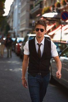 White shirt, black waistcoat, blue jeans, brown tie