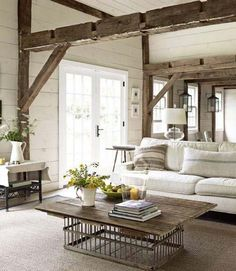 Living Room decor - rustic farmhouse style with exposed beam ceiling, interesting metal and wood coffee table, shiplap walls and neutral cream color palette.