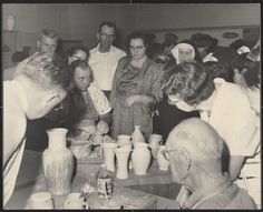 A black and white photograph of several adults including a nun looking at examples of pottery. 	Annie Belle Weaver Special Collections.
