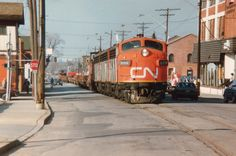 """Even the locals are a bit awe-struck as CN's """"Nanticoke"""" steel train rumbles up the middle of Ferguson Ave.N. in downtown Hamilton on its way up the hill thru Rymal, Caledonia, Hagersville and Garnet to the destination at the big steel facility on Lake Erie, about a 36 mile trip. Power this day is CN 9169, 9196, 9172 with a rather short train. Caboose at each end so power can run around train upon return.  Photographer:  Arnold Mooney"""