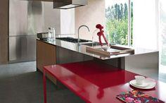 une table rouge et un îlot de cuisine métallique et fonctionnel
