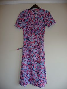 Description:Stunning blue, pink, purple floral print dress.concealed zip up left side. Belted.Pussy bow detail which can be removed. Ideal for the summer70s does 40sThe label states: Measurements (measure laid flat):across chest 18 inches / 46 cmsacross waist 14 inches / 36 cmsshoulder to hem 40 inches /102  cmssleeves shoulder to cuff 8 inches / 21 cmPostage/Packaging:We will try to use recycled packaging or the most cost effective packaging. If ...