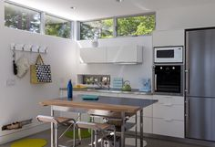Tenants Harbor ultra modern, prefab home features a small, horizontal sink window which echoes the clerestory windows, and do the horizontal cabinets