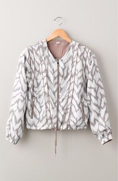 Two looks in one, this lightweight jacket printed with chevron stripes can be reversed to a softly luminous finish.