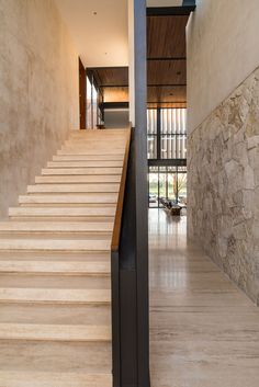 A large stone staircase leads to the upper floor in this modern house.
