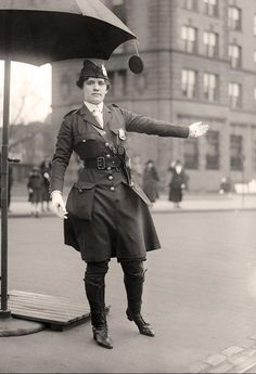 Traffic Cop. 1918. Notice that hte umbrella has a small mirror so she can see behind her.