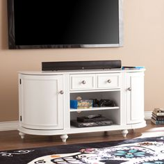 Build your family room around the delicate touches and lovely look of this TV/media stand. Truncated corners create a rounded edge where two, ornate side cabinets offer shelf storage for movies, games, or anything to be tucked away. Two broad