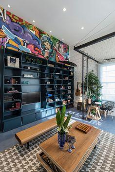 Decoração rústica e sofisticada de living jovem, Casa Cor, estante com nichos azuis, cadeira de madeira, mesa de madeira com vidro, parede de tijolinhos, rede-cama, plantas na decoração, mesa de centro de madeira e quadro, arte, grafite.