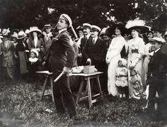 El Rey Alfonso XIII practicando un juego de azar durante un acto benéfico ante la divertida mirada de los presentes, incluyendo la Reina Victoria Eugenia (con sombrero de plumas blancas), su hija Beatriz, sus cuñados. Isle of Wight