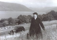 A traveling nurse makes her way up a grassy hill located in Argyle, Scotland in this lovely image from 1959. #nurse #uniform #vintage #1950s #fifties #Scotland #car