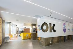 The café sits behind a logo wall of die-cut sheet metal, with tables and chairs by Workspacestudio.