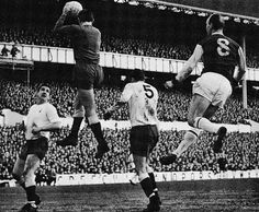 21st January 1967. Tottenham Hotspur goalkeeper Pat Jennings catching the ball before Burnley inside forward Andy Lochhead and helped by team mates Dave Mackay and Mike England, at White Hart Lane.