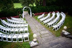 A simple beautiful look for a outdoor ceremony . White padded folding chairs with a plain white arch .