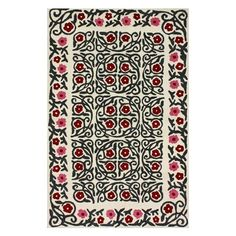 Wool rug in ivory with a tribal floral and vine motif. Hand-tufted in India.    Product: RugConstruction Material: 100...