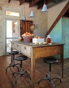 This kitchen work table looks like it could have been in  a library, school or even postoffice. Love the patina on the table and the stools are simple but are a perfect contrast to the rustic table.