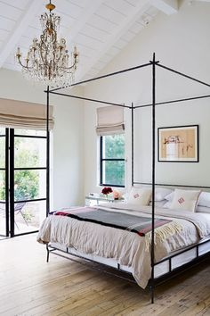 Modern Bedroom with Metal Four Poster in Bedroom design ideas. White bedroom with iron bed, chandelier and grey roman blinds, bed dressed with linen sheets and monogram cushions.