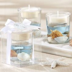 "Dazzle your wedding guests with these gorgeous tealight holders. This beach favor features real seashells that float in a blue gel. They are individually wrapped in a clear box decorated with a white ribbon and include a seashell-shaped tag that reads ""For You."" #BeachWeddingFavors #TealightHolderFavors #WeddingFavors"