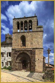 Photo de l'église romane Saint-Pierre d'Arlempdes du XIIe siècle avec son beau portail polylobé en plein cintre et son clocher à peigne rectangulaire du XVIe siècle muni de quatre arcades; à côté se trouve le Calvaire monumental du XVe siècle.