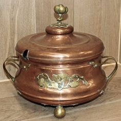 This unusually adorned soup tureen was fashioned from copper then fitted with brass mounts that create the handle for the lid, rose ornamentation, the handles and even the ball feet. Circa 1860s. Measures 16 x 18 x 14.