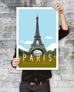 """Vintage Paris Travel Poster. 20 x 30. My original design celebrates The City of Lights (La ville des Lumières) and the iconic Eiffel Tower. The Paris Travel Poster is inspired by vintage designs from another era with retro styled typography. You'll love the festive red flag fluttering on top! 20"""" x 30"""". Does not include frame. Heavy matte paper."""