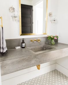 Mixed metals work well in this contemporary bathroom alongside a contrasting grey polished concrete basin. Love the touch of glam from the gold taps and mirror. The patterned floor tiles add another dimension.The grey, black, white and gold colour palate work so well.