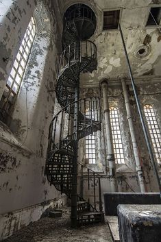 Vertigineux escalier en hélice tout en métal noir de style Eiffel, dans un intérieur industriel abandonné.