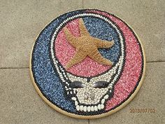 """#Handmade #GratefulDead: Steal Your Face with Starfish #wallhanging. 18"""" diameter pinewood base. Image made with sea shells, starfish, and beans."""