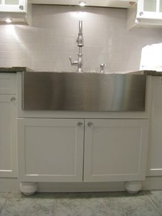 Example of stainless apron front sink in traditional white kitchen. I like it, and definitely easier to maintain than a porcelain sink.