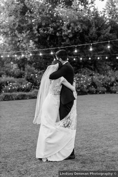 black and white wedding photography, couple portrait under string lights, lace dress & mid-length veil