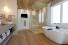 Bad, Bodengleiche Duschwanne, Freistehende Badewanne, Fußboden in Holzoptik, Decke mit Holzpaneelen, Wände weiß, Wandfliesen beige, Fenster über Badewanne