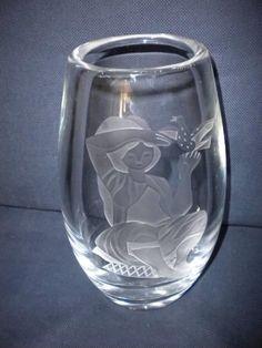 Stor, flott Hadeland glassvase. Signert. Stor, tung glassvase fra Hadeland. Høyde 23,5 cm. Vekt 2,4 kg. Signert nede på kanten bak: Hadeland - 59. H.B. 592. Motivet (jente med fugl i hånden) er formgitt av Hermann Bongard, en av våre mest kjente glasskunstnere