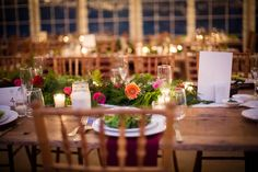 Glowing votives, graceful greenery and vibrant blooms for dramatic and festive centerpieces at Amy and Saad's Anthony Wayne House wedding: Femina Photo and Design.
