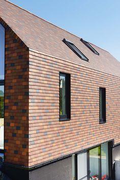 Maison familiale d'un seul tenant (Zampone Architectuur, Sint-Jans-Molenbeek). La maison a été conçue comme un socle massif surmonté d'un volume supérieur entièrement revêtu de tuiles plates. Pour revêtir tant le toit que les façades, le choix s'est porté sur des tuiles plates Koramic dans un mélange de teintes de terre. Des éléments adaptés créent une transition parfaite entre la façade et le toit. L'utilisation de diverses teintes de teintes de rouge confère à la maison un aspect…