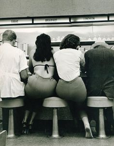 Two women share a stool at the diner, 1950s.