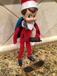 """You guys, Arthur is the cutest little skater elf today! (My new favorite!)  Arthur is getting ready to shred & jam out. #elfontheshelf #boymom  Backpack: Vans keychain.  Phone: """"My Life"""" doll prop Shoes & Glasses: Barbie / Ken accessories. Skateboard: Kids toy."""