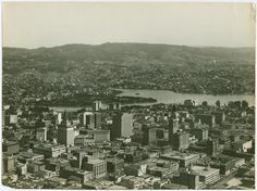 Aerial view of Oakland, California showing Lake Merritt immediately adjacent the business district; wooded hills of residential sections in background. (ca. 1926)