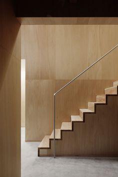 Scala in legno minimalista mimetizzata in una stanza completamente rivestita in pannelli di legno. Spiccano solo i gradini e la semplice ringhiera metallica